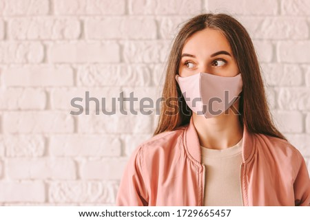 Portrait happy young woman in trendy medical face mask look at copy space. Beautiful stylish hipster girl in pink protective face mask and jacket. Cool fashionable girl. COVID-19 quarantine lifestyle #1729665457