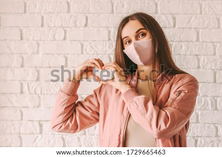 Portrait happy trendy hipster girl in pink medical face mask show heart shape symbol with hands. Young beautiful millennial woman in stylish protective face mask gesturing love peace sign with fingers #1729665463