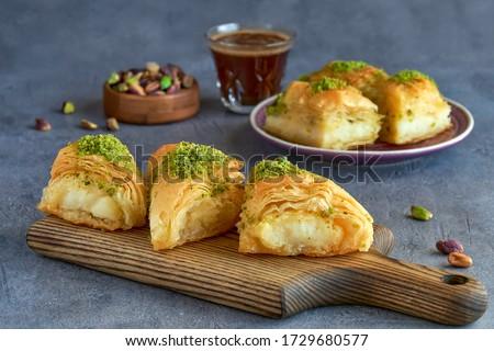 Sweets arabic dessert kunefe, kunafa, kadayif with pistachio and cheese                             Royalty-Free Stock Photo #1729680577