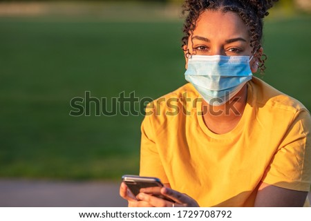 Mixed race biracial African American teenager teen girl young woman wearing a face mask and using mobile cell phone outside during the Coronavirus COVID-19 virus pandemic #1729708792