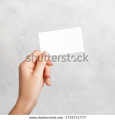 Female hand holding a blank business card, cutaway on gray concrete background with copy space. Mockup