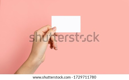 Female hands with cutaway, blank menu, discount card, business card on color pink beauty background with copy space. Template for design Mockup