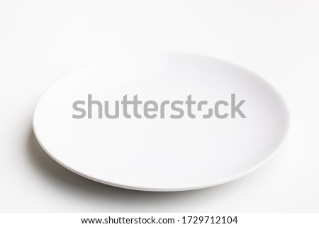 An empty white plate on white background. Royalty-Free Stock Photo #1729712104