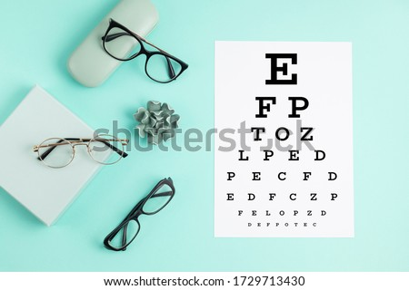 Collection of eyeglasses with eye test table. Optical store, glasses selection, eye test, vision examination at optician, fashion accessories concept. Top view, flat lay Royalty-Free Stock Photo #1729713430