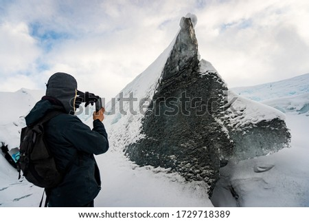 Adventurer hiker taking a picture of a rock, piece of ice with the shape of a wolf / dog raising from the snow in Matanuska Glacier, Anchorage, Alaska. It's the call of the wild.