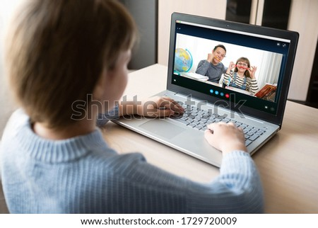 A girl with a laptop communicates with friends via video call. Online remote learning. Social distance. Homeschooling during the quarantine, and the outbreak of coronavirus. #1729720009