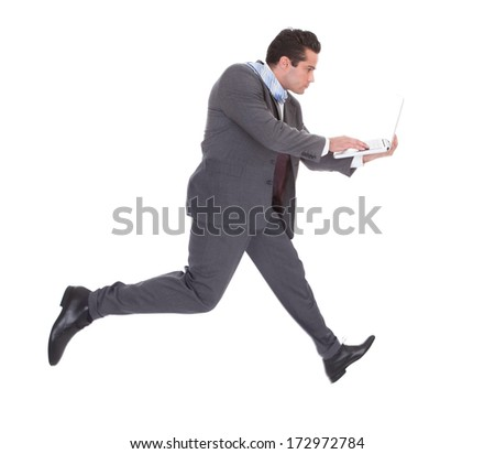 Young Businessman In Hurry Using Laptop While Running Over White Background #172972784