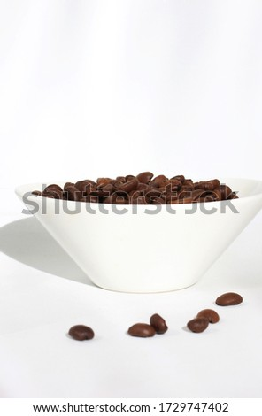 Arabica coffee beans and dark roasted in a white bowl. Bright picture for advertising a coffee shop or a menu of coffee drinks.