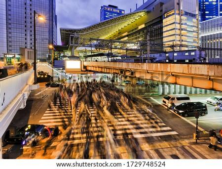 Crowded street crossing in Osaka city near OSaka umeda railway train station at sunset. Royalty-Free Stock Photo #1729748524