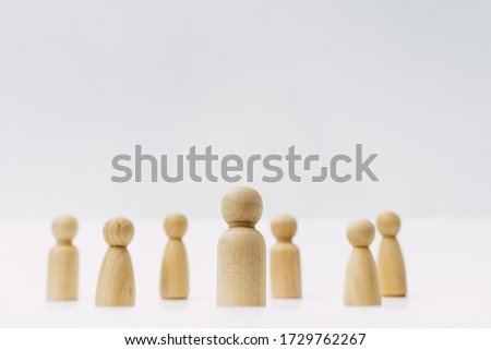 Small group of separated people seen from above represented anonymous with wooden figures on white background. #1729762267