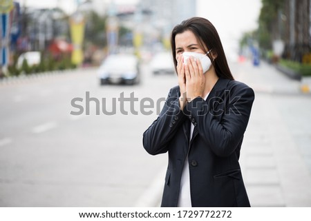 Close up of a businesswoman in a suit wearing Protective face mask and cough, get ready for Coronavirus and pm 2.5 fighting against beside road in background. #1729772272
