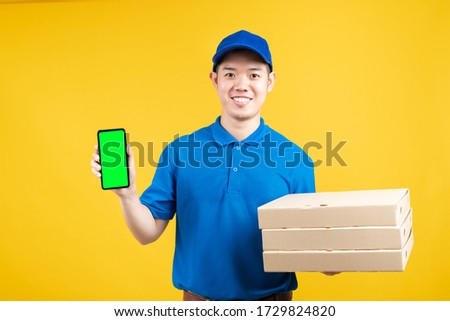 Delivery asian male presentation order pizza in box with smartphone green screen delicious fast deliver to receiver shipping buying online on yellow background isolated studio shot.