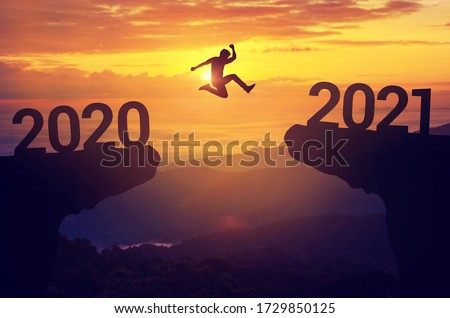 Silhouette man jump between 2020 and 2021 years with sunset background, Success new year concept. Royalty-Free Stock Photo #1729850125