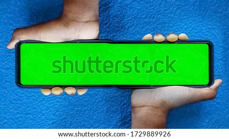 Merged Double screen mobile smart phone in green color and boy holding on his hand with Isolated on blue background. Doble Mobile phone screen on blue background with space for text.