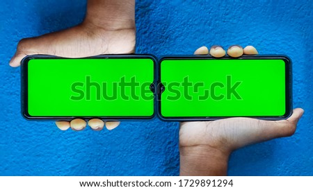 Double screen mobile smart phone in green color and boy holding on his hand with Isolated on blue background. Doble Mobile phone screen on blue background with space for text.