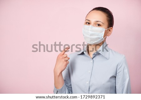 portrait of a woman in a protective respiratory mask on a pink background, pointing at the mask. #1729892371