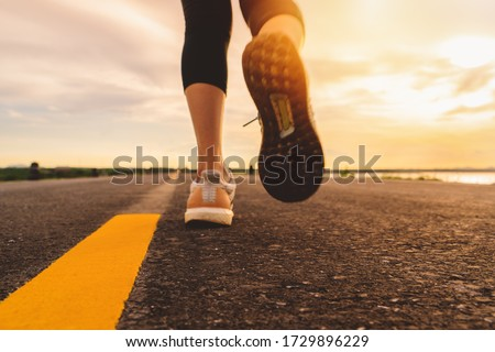 Athlete running on the road trail in sunset training for marathon and fitness. motion blur of woman exercising outdoors #1729896229