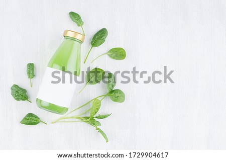 Bright green spinach juice in glass bottle with blank label, greens on white wooden board, top view, copy space, template for design, advertising, portfolio. #1729904617