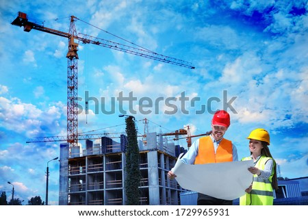 Construction crane and unfinished building against blue sky. Space for text #1729965931