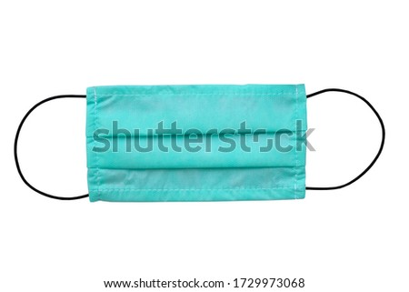 Green medical mask on a white background isolate. Disposable face mask with black elastic bands for the ears. Remedies during the epidemic of coronavirus, environmental pollution. #1729973068