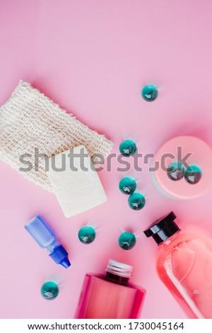 A set of toiletries, jars of body cosmetics. Deodorant, shampoo, spray, cream, scrub, bath balls on a pink background. Personal care concept. #1730045164