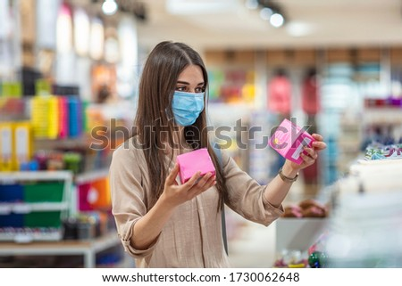Girl shopaholic in mall. Sale, discount, coronavirus COVID-19, copy space. Young woman shopping in supermarket with shopping cart wearing medical face mask to protection the COVID-19 virus.