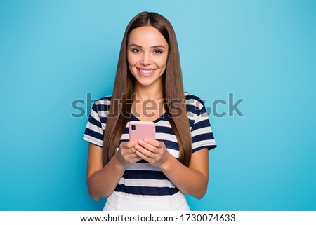 Photo of cheerful pretty lady hold telephone hands reading email check blog comments reactions followers wear striped t-shirt white skirt isolated blue color background #1730074633