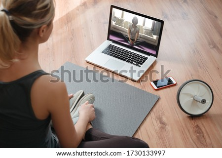 Yoga teacher conducting virtual class at home on a video conference. Young beautiful woman doing an online yoga class in her living room with laptop. Home fitness and workout concept #1730133997