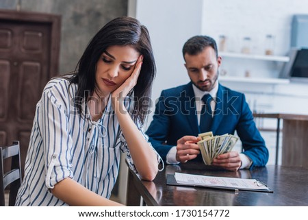 Selective focus of upset woman near documents with collector counting dollar banknotes at table in room #1730154772