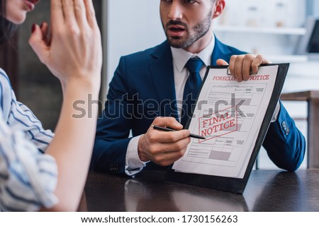 Cropped view of woman and collector pointing with pen at documents with foreclosure and final notice lettering at table Royalty-Free Stock Photo #1730156263