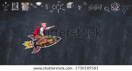 Back to school. Boy flying on rocket from colorful pencils and pointing up.