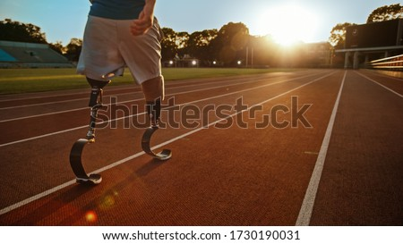 Athletic Disabled Fit Man with Prosthetic Running Blades is Walking During a Training on an Outdoor Stadium on a Sunny Afternoon. Amputee Runner Preparing for a Run. Motivational Sports Shot. Royalty-Free Stock Photo #1730190031