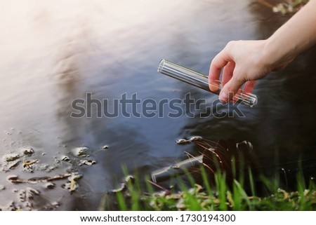 Scientist and biologist hydro-biologist takes water samples for analysis outdoors. Hand is collects water in a test tube. Pond water pollution concept.
