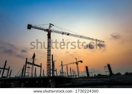 New construction site with cranes on orange sunset, sunrise sky background. Steel frame structure, structural steel beam build large buildings at construction site . construction machinery. #1730224360