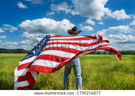 Man wearing cowboy hat waving American flag standing in grass farm agricultural field blue sky white clouds,  holidays, patriotism, pride, freedom, conservative, political parties, immigrant #1730256877