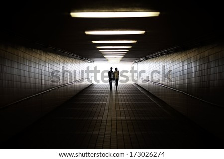 Young couple in silhouette walking towards exit of pedestrian underpass #173026274