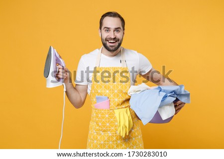 Cheerful young man househusband in apron hold basket with clean clothes, iron doing housework isolated on yellow background studio portrait. Housekeeping concept. Mock up copy space. Looking camera