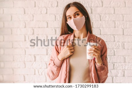 Happy hipster girl in stylish medical face mask and jacket drink coffee from paper cup. Beautiful trendy woman in pink protective face mask hold disposable cup of coffee or tea. Quarantine lifestyle #1730299183