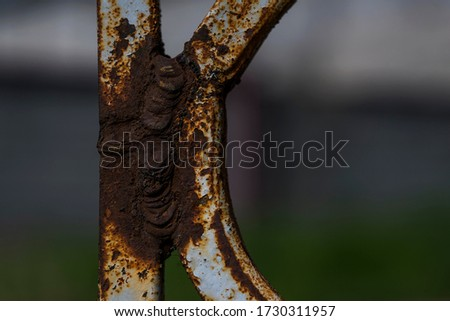 Rust on metal. Fragment of a rusty metal fence made of rods. Rust on welding parts. Red rusty stains on iron. Rust texture. Macro photo. Abstract grunge background #1730311957
