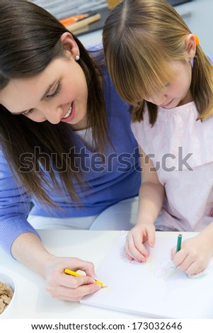 Child drawing with crayons with her mom, sitting at table in kitchen at home #173032646