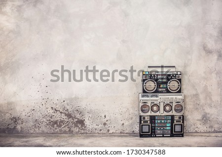 Retro old school design ghetto blaster boombox stereo radio cassette tape recorders from 80s front concrete wall background. Nostalgic Rap, Hip Hop, R&B music concept. Vintage style filtered photo #1730347588
