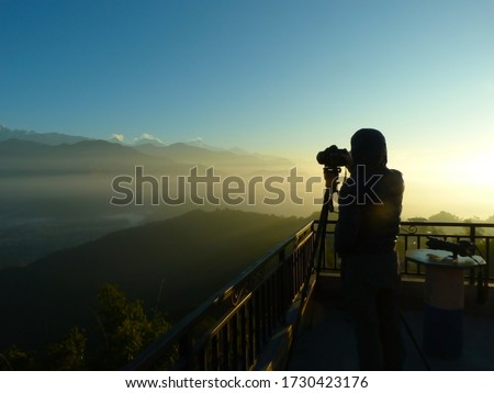 a photographer taking picture of mountain landscape in a misty golden sunrise.