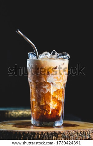 Cold fresh thai ice tea coffee served with coconut milk and metal straw with ice cubes on wood table and black background  #1730424391