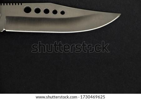 Closeup photo of a shiny and sharp hunter knife on the black background.