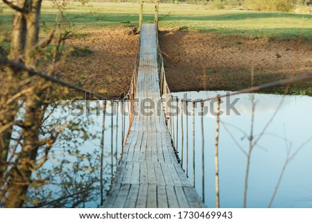 Old suspended wooden foot bridge over the river. Photo on a summer day. River crossing for people #1730469943