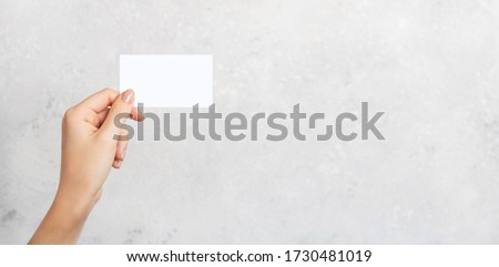 Female hand holding a blank business card, cutaway on gray concrete background with copy space. Branding mockup template. Mockup