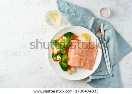 Steam salmon and vegetables, Paleo, keto, fodmap, dash diet. Mediterranean diet with steamed fish. Healthy concept, white plate on gray table, gluten free, lectine free, top view #1730494033
