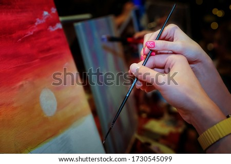 Hands of loving couple holding paint brush, touching and creating a nice picture of sunset. Man and woman paint their picture of sunset on the seashore. Art workshop. Make a date to draw a picture
