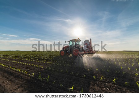 Tractor spray fertilize field with insecticide herbicide chemicals in agriculture field  #1730612446