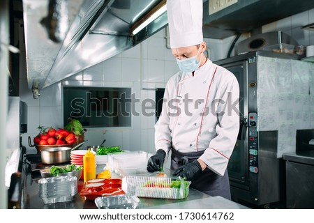 Food delivery in the restaurant. The chef prepares food in the restaurant and packs it in disposable dishes #1730614762